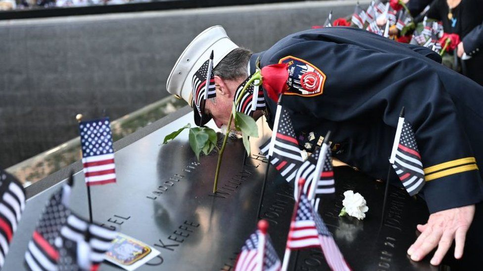 Retired Paramedic Chief Charlie Wells kisses the name of a relative killed in the attack on the World Trade Center