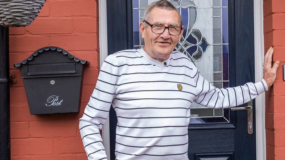 a man in a striped top standing by a door
