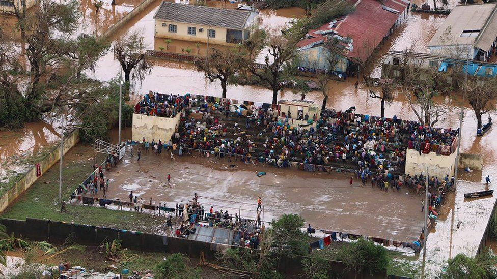 People in the flooded Mozambique town of Buzi stranded on a football stand.
