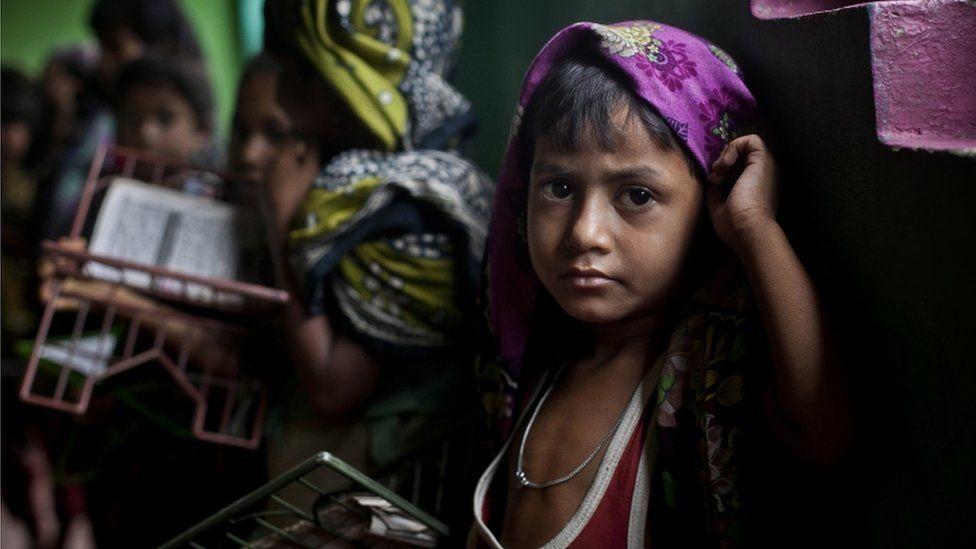 SHAMLAPUR, BANGLADESH - JULY 4: A Rohingya child holds a Koran during class at a madrassa in an informal settlement July 4, 2015 in Shamlapur, Bangladesh.
