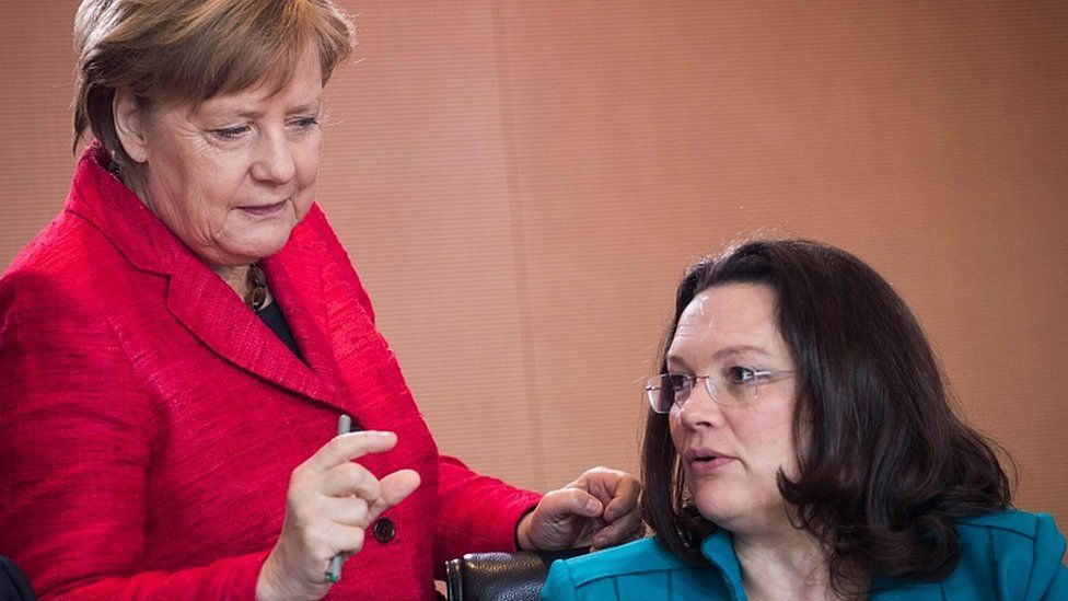 File image of German Chancellor Angela Merkel (L) speaking to Andrea Nahles on 29 March 2017