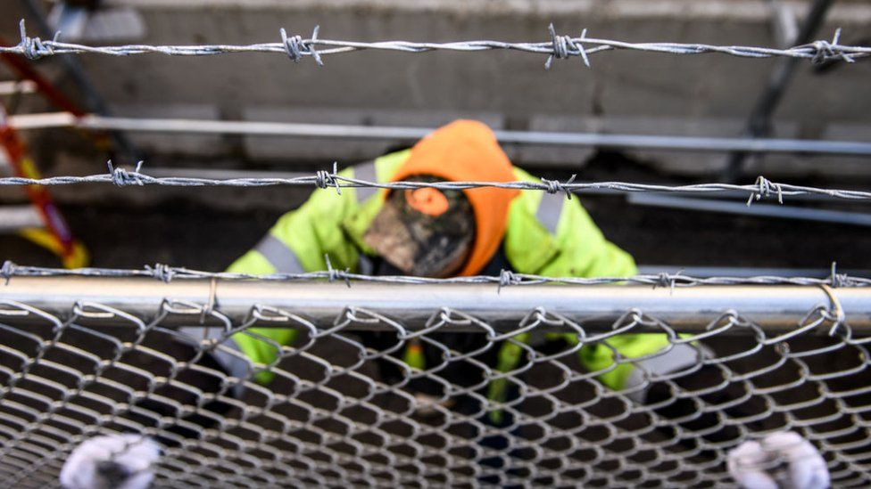 Crews install fencing outside the Hennepin County Government Center