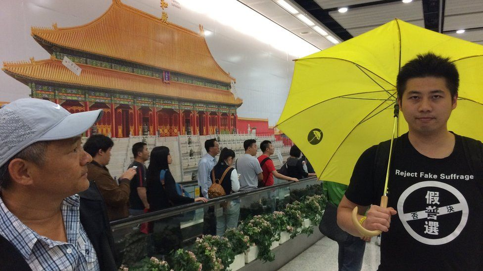 """Billboard-sized image of the Forbidden City with passers-by and a man with a yellow umbrella and a T-shirt reading """"reject fake suffrage"""", in front."""