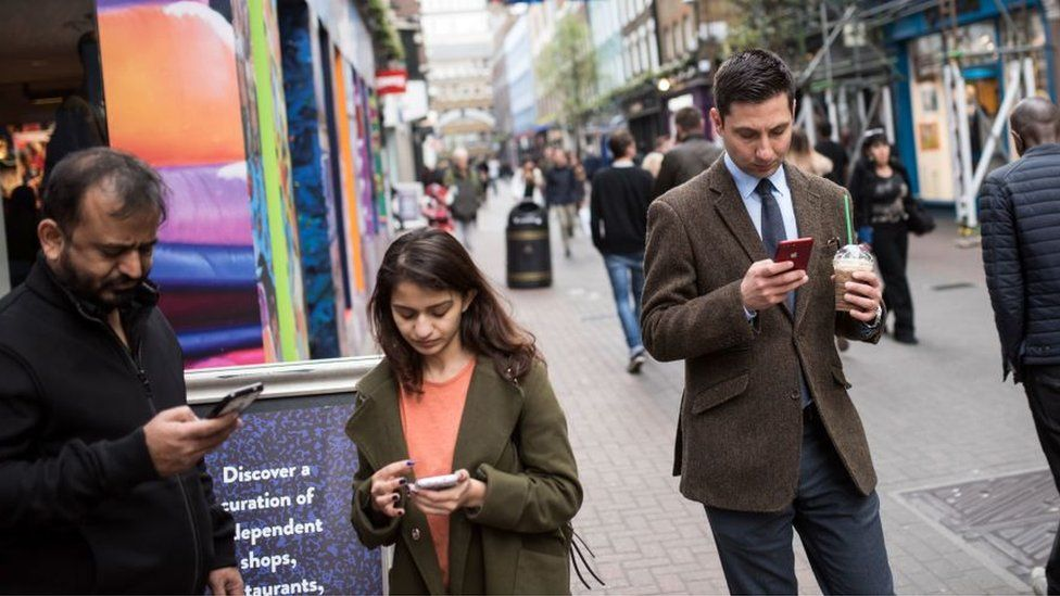 Members of the public check their mobile phones as they stand on Carnaby Street in London, on March 28, 2017.