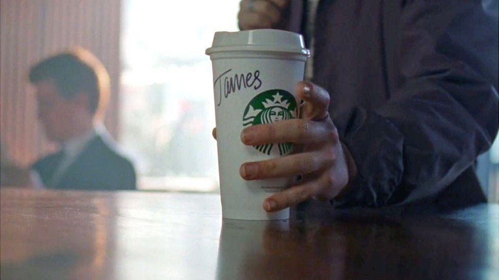 Starbucks customer holds coffee