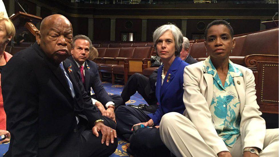 Miembros de la Cámara de Representantes sentados en el suelo para exigir acción en materia de legislación sobre las armas.