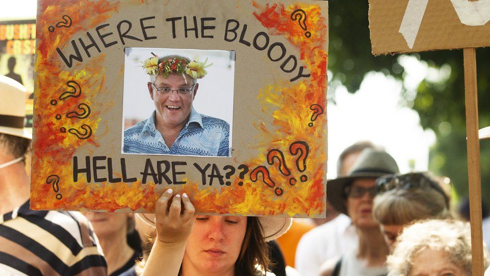 "A protester in Sydney holds up a sign outside the Prime Minister's home showing a picture of Scott Morrison and a message: ""Where the Bloody Hell Are Ya?"""