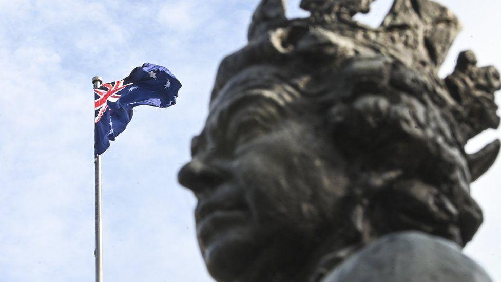 Statue of Queen Elizabeth next to an Australian flag