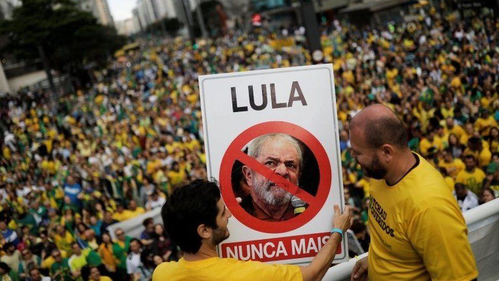 "Supporters of Jair Bolsonaro hold a sign with the image of former Brazilian President Luiz Inácio Lula da Silva reading ""Lula, never again"""