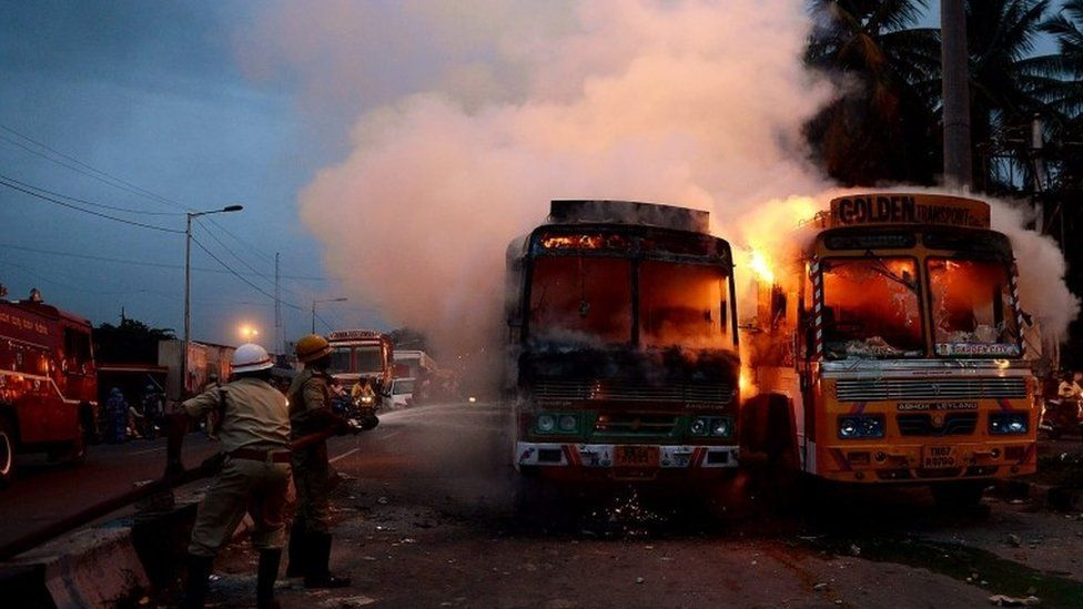 Indian fire fighters extinguish lorries set to fire by pro-Karnataka activists (unseen) during a protest in Bangalore, India, 12 September 2016.