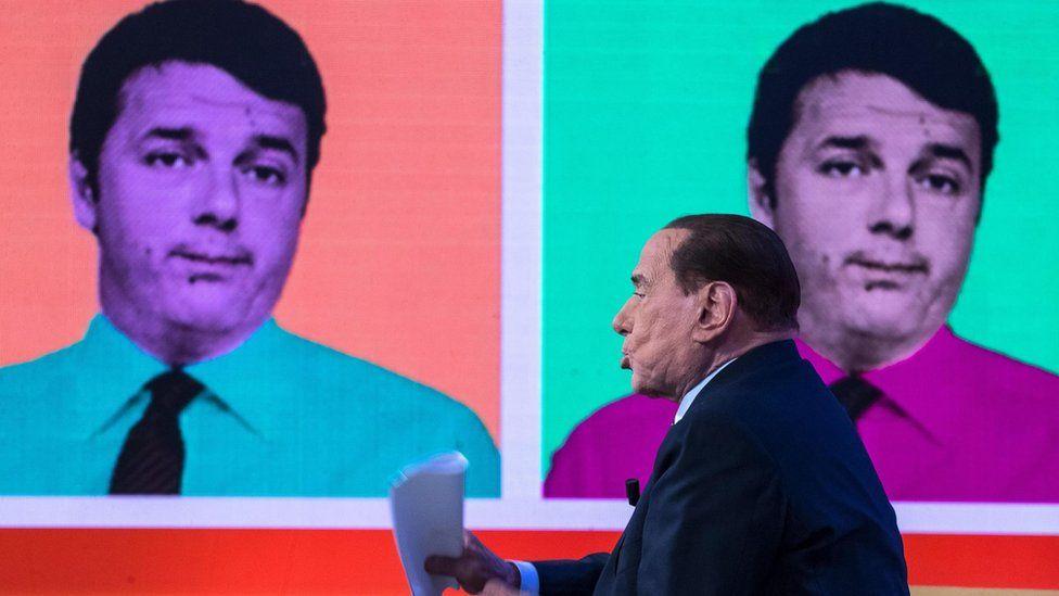 Former Italian prime minister Silvio Berlusconi speaks during a TV studio debate next to the backdrop of the former Italian prime minister Matteo Renzi