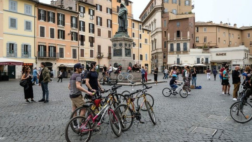 Cyclists stop in the Camp di Fiori square in central Rome, Italy. Photo: 16 May 2020