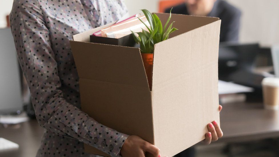 Woman holding box of belongings
