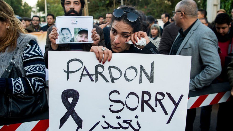 Moroccans attend a vigil for the murdered tourists