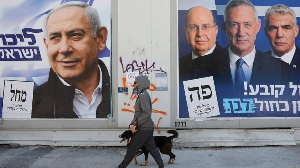 A man walks with his dog between election campaign billboards of Prime Minister Benjamin Netanyahu (L) and leaders of the Blue and White party Benny Gantz (2-R) and Yair Lapid (3-R) and Moshe Ya'alon (R), in Tel Aviv, Israel, on 3 April 2019