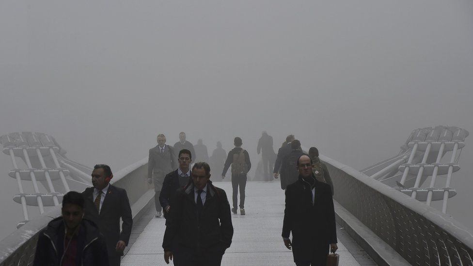 Commuters walk across Millennium Bridge over the Thames