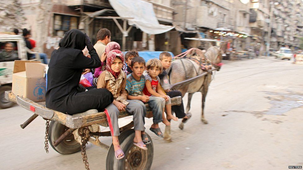 A family travels through Aleppo on a horse-drawn cart (27 June 2015)