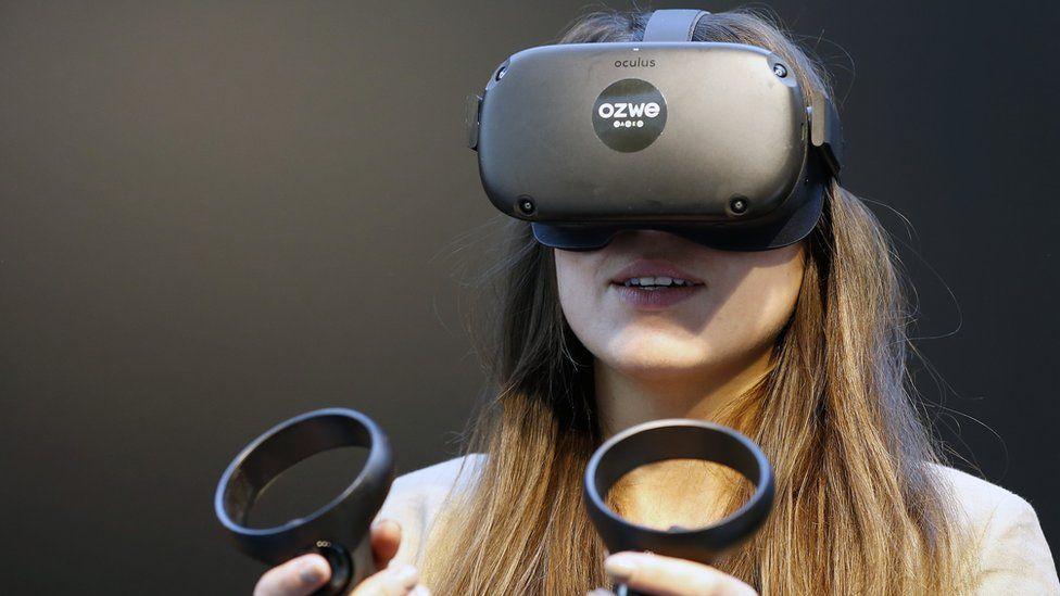 A woman wears a black first-generation Oculus Quest headset