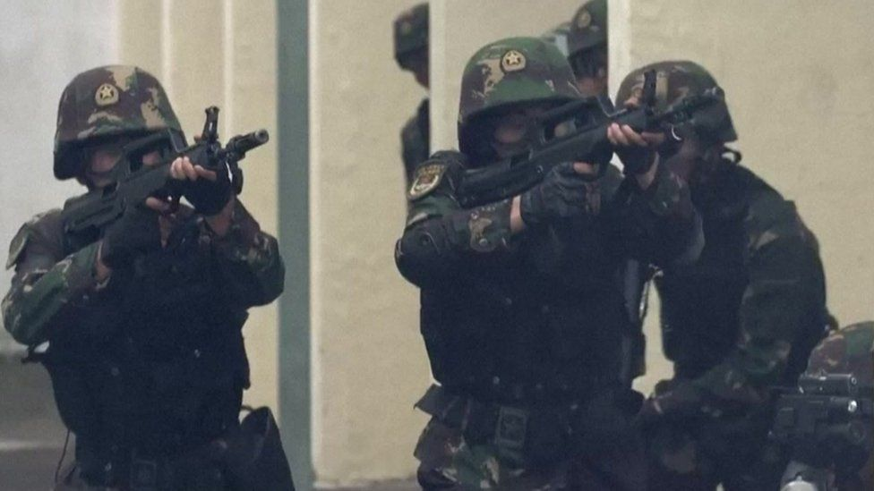 Screen grab from the PLA's anti-riot video - shows soldiers pointing guns