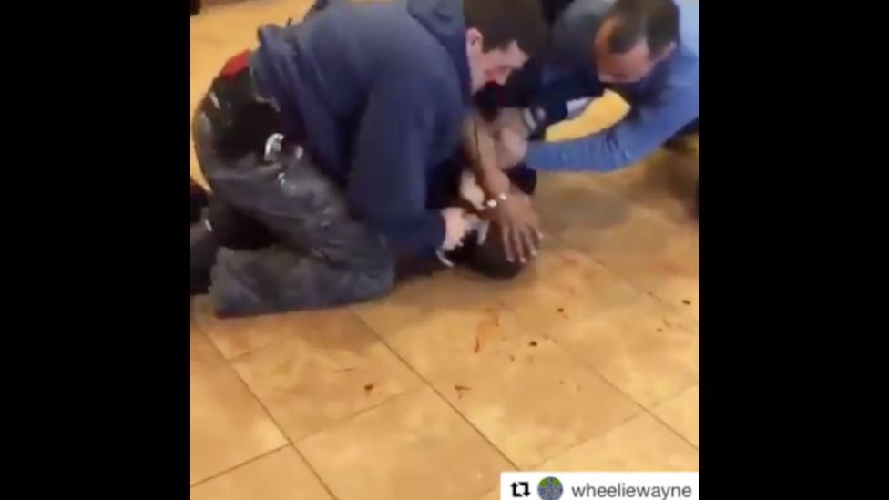 White policemen hold down a black man on a blood spattered floor