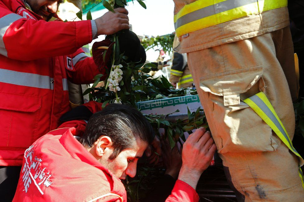 Firemen mourn beside a lorry carrying the coffins of colleagues who were killed in the Plasco building collapse is surrounded by mourners in Tehran (30 January 2017)
