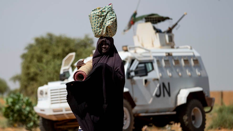 A woman in Mali near a UN vehicle
