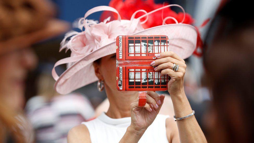 женщина в розовой шляпке делает селфи