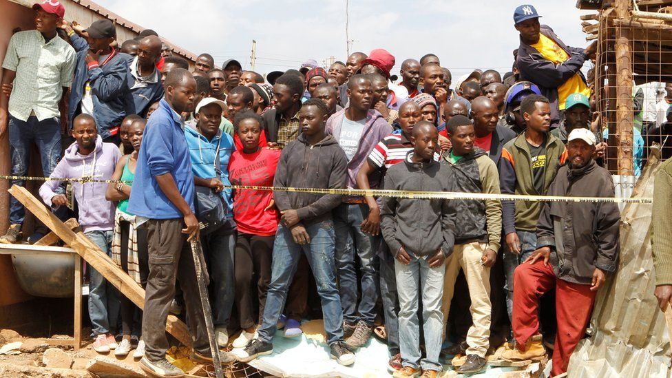 Kenyans watch as rescue teams and police officers search the debris