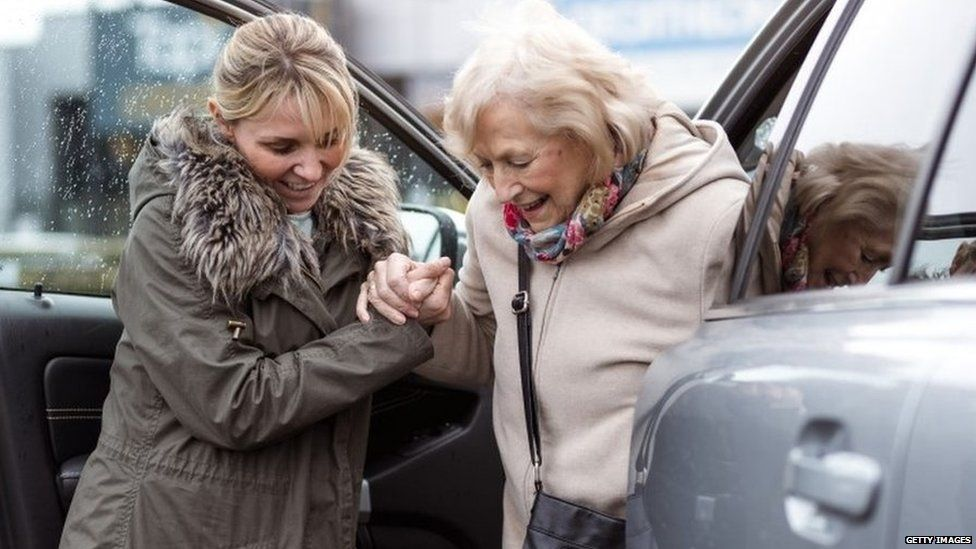 Young lady helping older woman out of a car