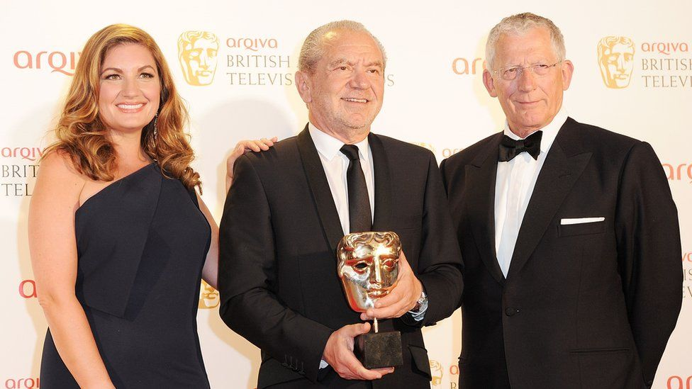 Karren Brady, Lord Alan Sugar and Nick Hewer pose in front of the winners boards at the Arqiva British Academy Television Awards 2012
