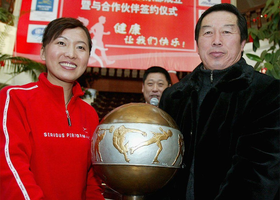 Olympic long-distance running champion Wang Junxia (L) poses for pictures holding an award with her teacher, former China track coach Ma Junren during an opening ceremony of Wang's Running Club on 25 January 2005 in Shenyang of Liaoning Province, China.