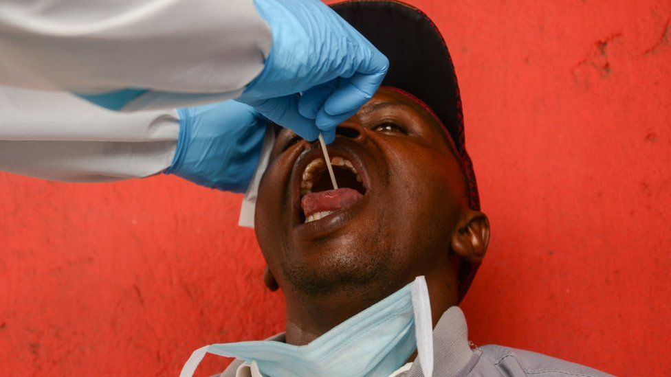 A health worker performs a mouth swab test on a resident during the corona virus pandemic.