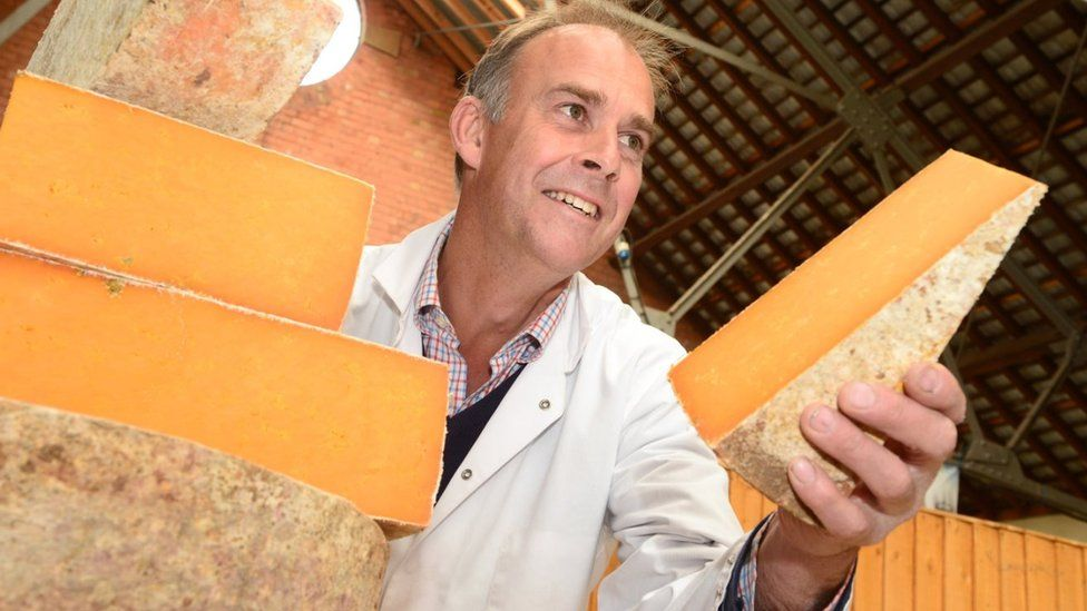 Cheese maker holds cheese