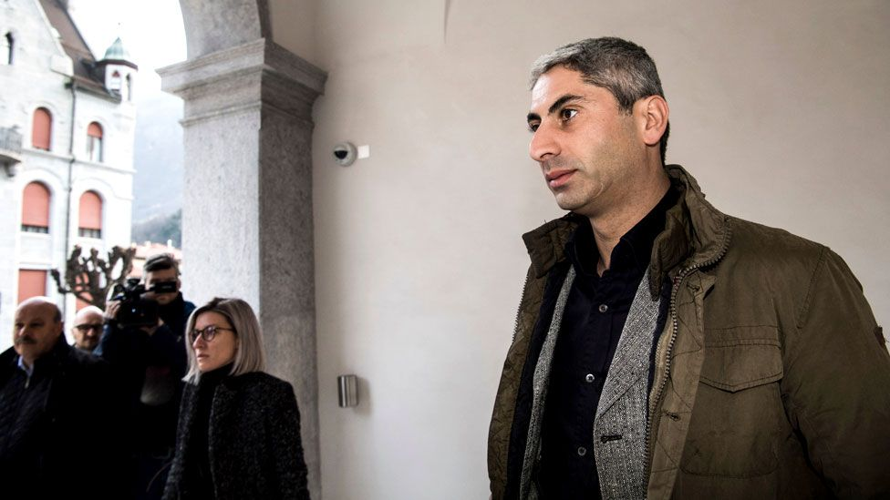 Cosar, clean-shaven and in civilian clothing, arrives at the Federal Criminal Court of Switzerland in Bellinzona