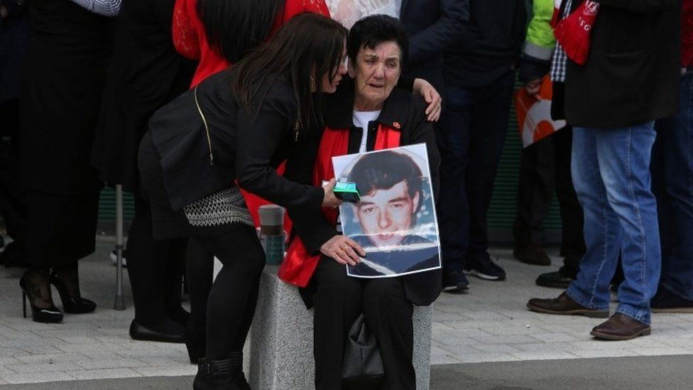 A woman holds an image of a victims of the 1989 Hillsborough disaster, as she reacts following the conclusion of the inquest into the disaster
