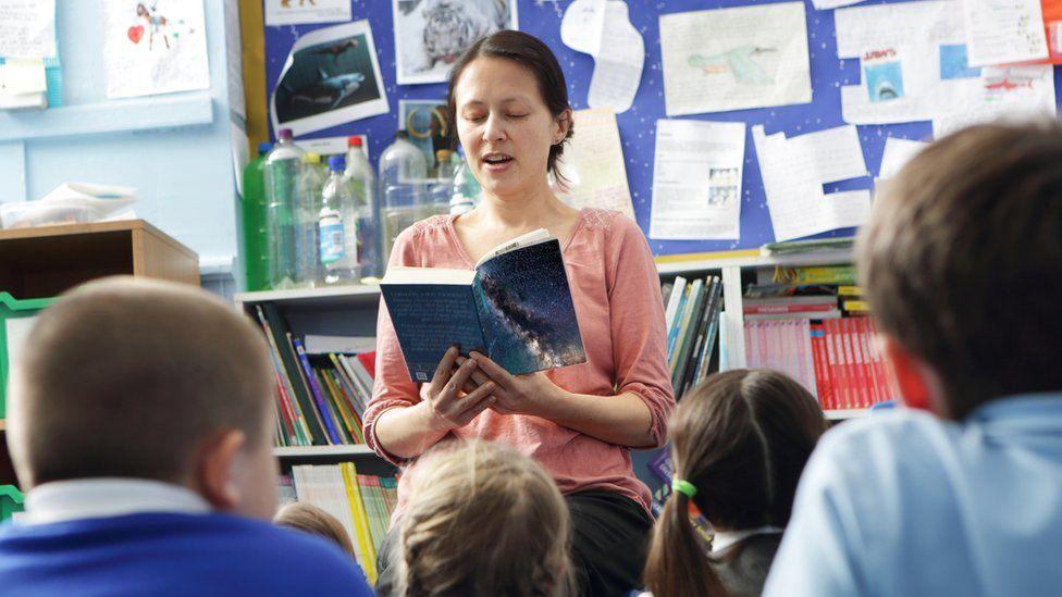 Teacher reading to children (stock image)