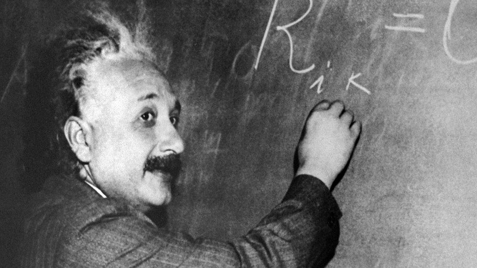 Albert Einstein writing on a blackboard