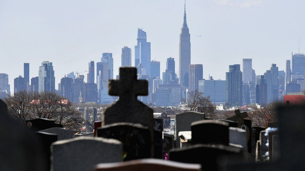 Gravestones from a cemetery are seen with the Manhattan skyline