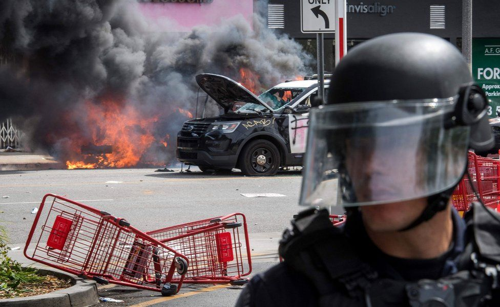 Police vehicles burn after being set on fire by demonstrators in the Fairfax District of Los Angeles as they protest the death of George Floyd, 30 May 2020