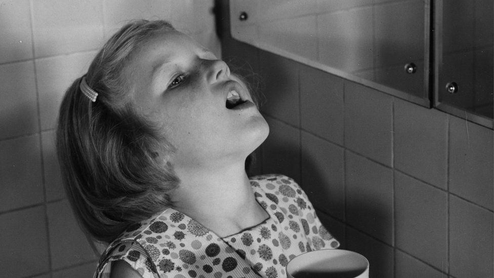 Plentyn yn garglo i geisio osgoi ffliw 1957