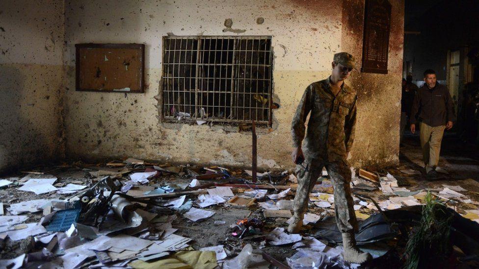 A Pakistani soldier walks amid the debris