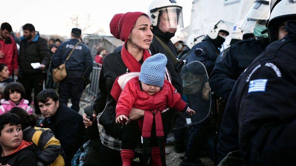 A woman looks for her husband and son as she is allowed to cross into Macedonia at the Greek-Macedonian border, near the Greek village of Idomeni. 2 March 2016