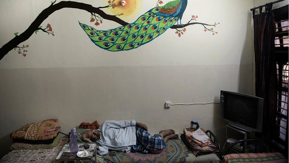 Mr Parameswar lying down on a bed in his room at the care home