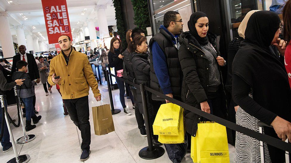 Customers queue outside a designer stall during the Boxing Day sale at Selfridges