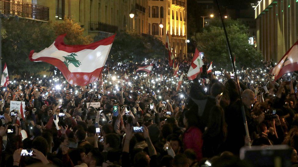 Demonstrators use their phone lights during an anti-government protest in Beirut