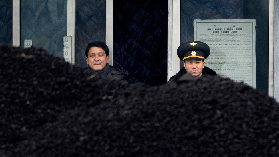 This file picture taken on 14 December 2012 from China's north-eastern city of Dandong, looking across the border, shows a North Korean military officer (R) and a North Korea man (L) standing behind a pile of coal along the banks of the Yalu River in the northeast of the North Korean border town of Siniuju