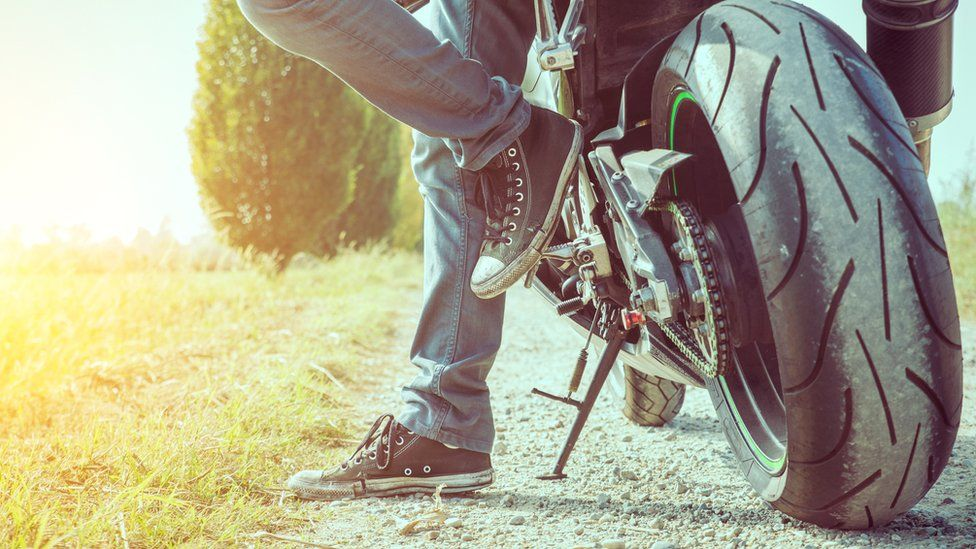 A motorcyclist in jeans and trainers