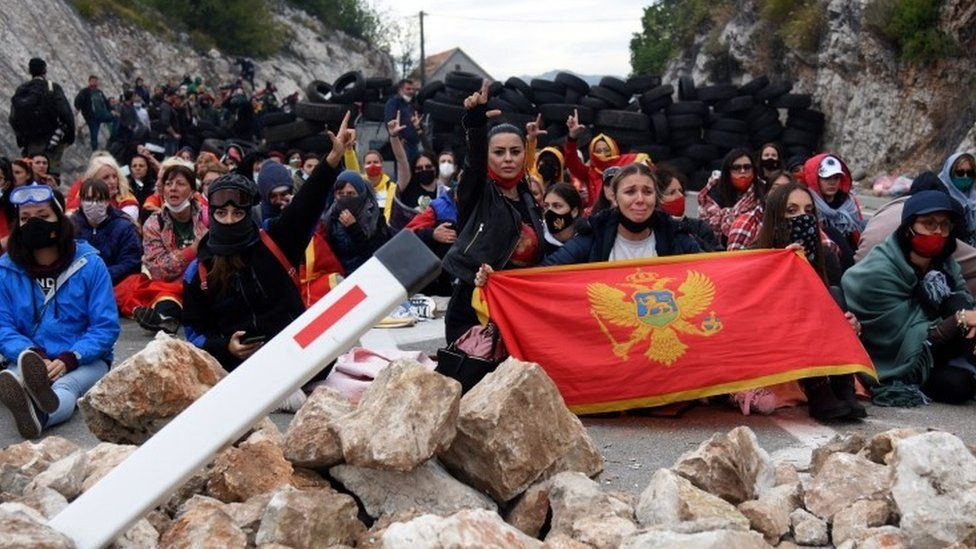 Protesters hold flags at a road block in Montenegro