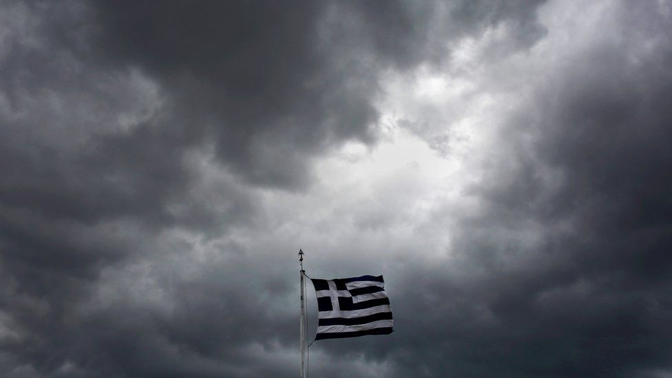 Greek flag against backdrop of stormy sky