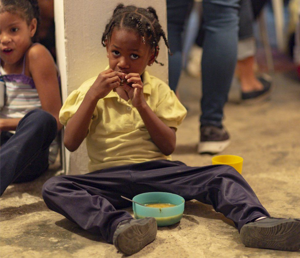 Child eating at social programme in Caracas